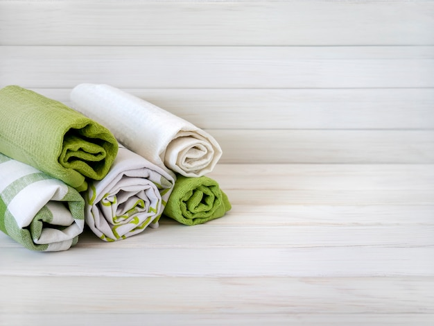 Uma pilha de toalhas cuidadosamente dobradas feitas de tecidos naturais em uma mesa de madeira