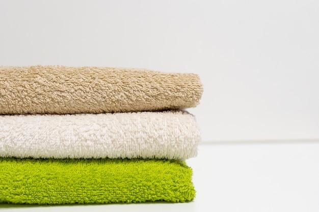 Uma pilha de toalhas multi-coloridas em um fundo branco.