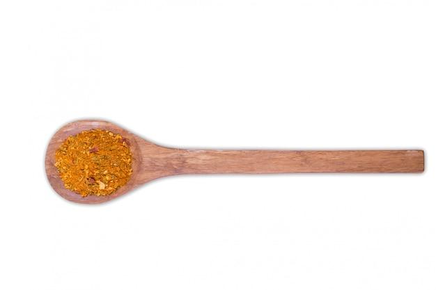 Uma pilha de uma mistura amarela da especiaria para a galinha na colher de madeira isolada no branco. especiarias consistem de páprica cebola alho mostarda coentro tomilho aipo açafrão erva-doce pimenta preta