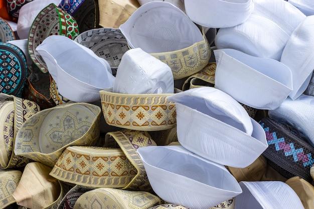 Uma pilha de vários bonés taqiyah projetados ou boné de oração muçulmano