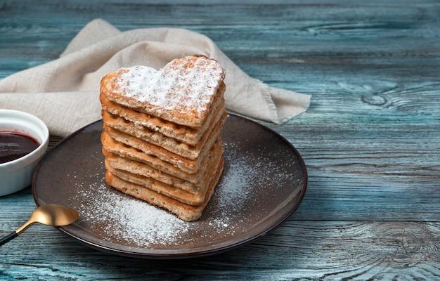 Uma pilha de waffles em forma de coração polvilhados com açúcar de confeiteiro em um fundo de madeira.