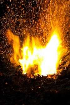 Uma pilha enorme de chamas vermelhas e amarelas com brasas voando.