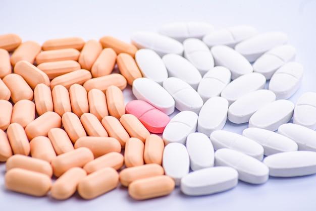 Uma pílula vermelha e muitas brancas e bege.