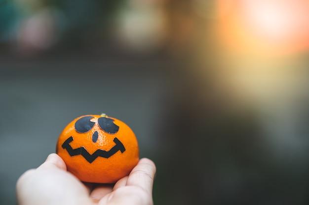 Uma pintura de cara de abóbora laranjas com assustador no dia da festa de halloween na mão