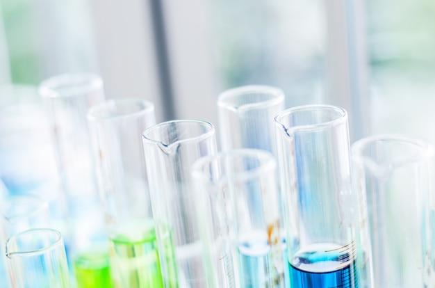 Uma pipeta soltando amostra em um tubo de ensaio, fundo de ciência abstrata