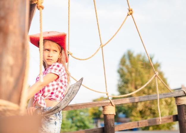 Uma pirata menina séria e engraçada com uma camisa xadrez e shorts jeans se agarra às cordas do navio
