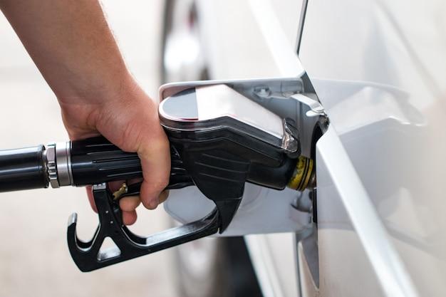 Uma pistola de reabastecimento no gargalo de um carro-tanque a gasolina.
