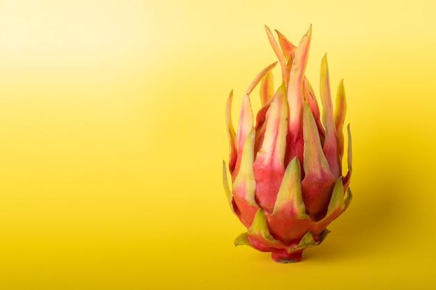 Uma pitaya colocada em verrtcal sobre um fundo amarelo.