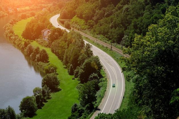 Uma pitoresca estrada sinuosa se estende ao longo da margem do rio, ao lado dos trilhos