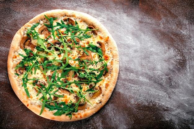Uma pizza inteira com rúcula, queijo, cogumelos porcini e óleo de trufas. receita de pizza italiana em um fundo marrom de madeira. vista superior e espaço de cópia