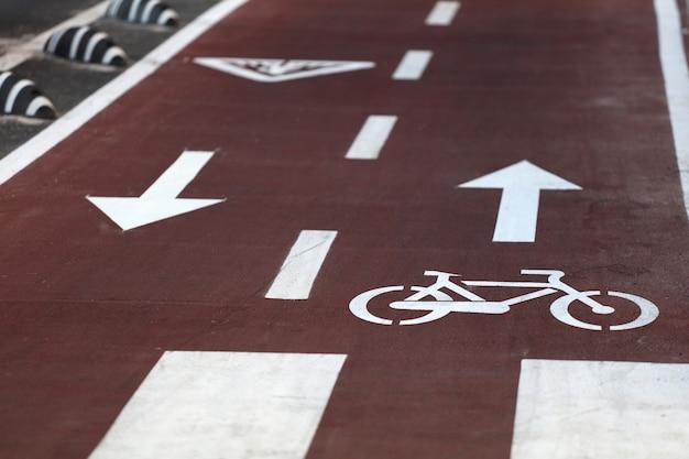 Uma placa branca de ciclovia em uma superfície de asfalto de uma estrada municipal na zona de segurança para bicicletas em primeiro plano