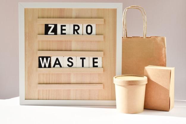 Uma placa com a inscrição zero desperdício com saco de papel e recipientes descartáveis