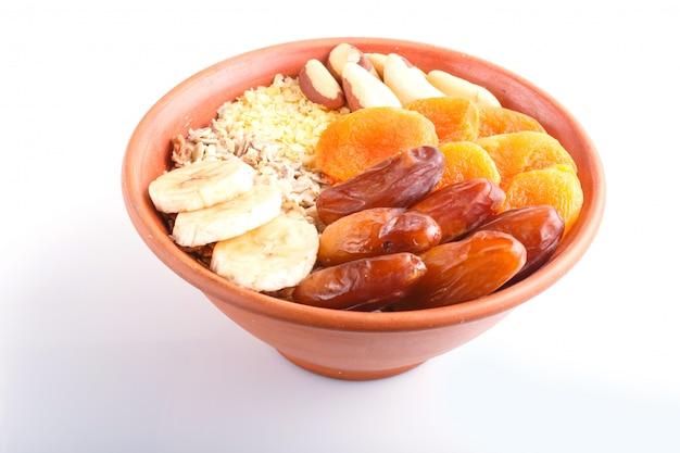 Uma placa com muesli, banana, abricós secados, datas, castanhas do brasil isoladas em um fundo branco.