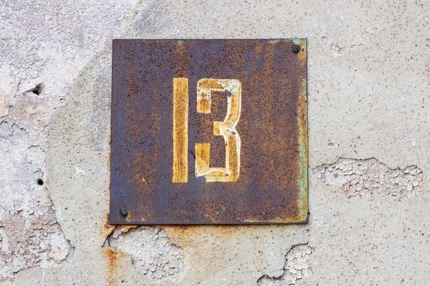 Uma placa com o número treze na parede da casa, número do infeliz