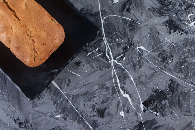 Uma placa com pão fresco de passas colocado sobre um fundo de mármore.