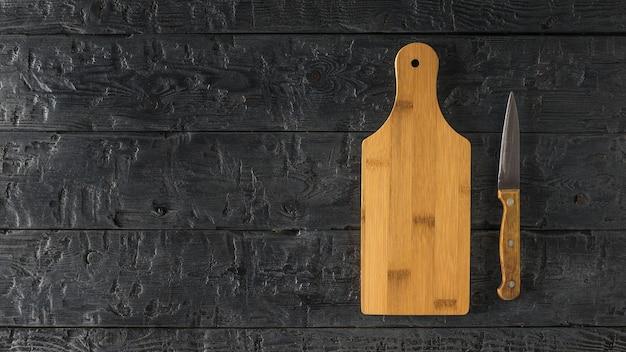 Uma placa de corte e uma faca com cabo de madeira em uma mesa de madeira preta.