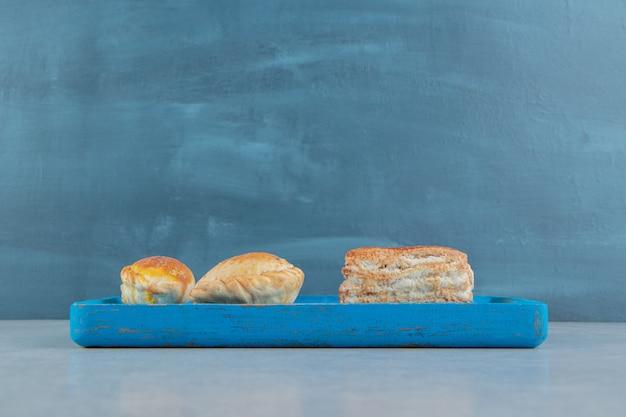 Uma placa de madeira azul cheia de biscoitos doces.