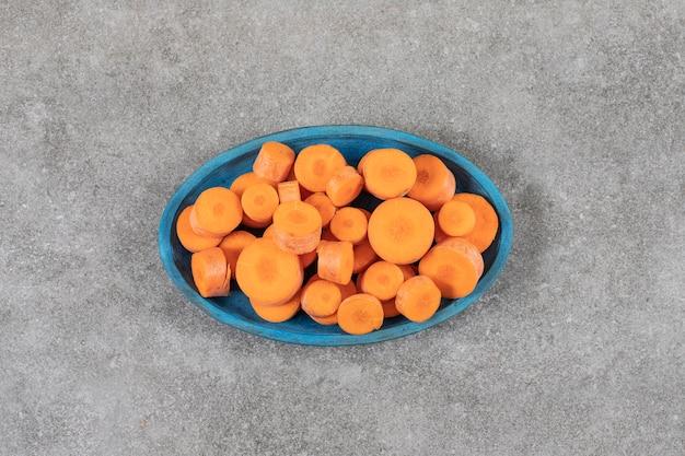 Uma placa de madeira azul cheia de cenouras fatiadas colocadas sobre uma superfície de pedra.