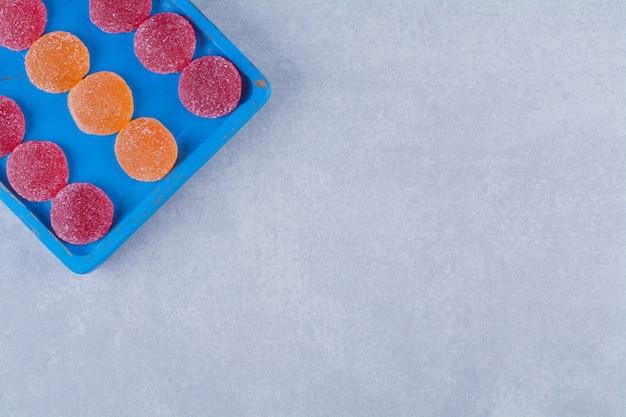 Uma placa de madeira azul cheia de geleias açucaradas de vermelho e laranja. foto de alta qualidade