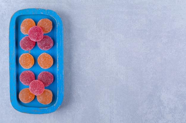 Uma placa de madeira azul cheia de geleias açucaradas de vermelho e laranja.