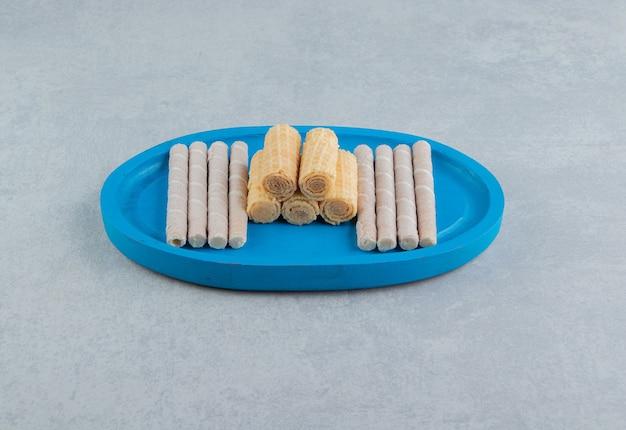 Uma placa de madeira azul cheia de rolos de waffle crocantes.
