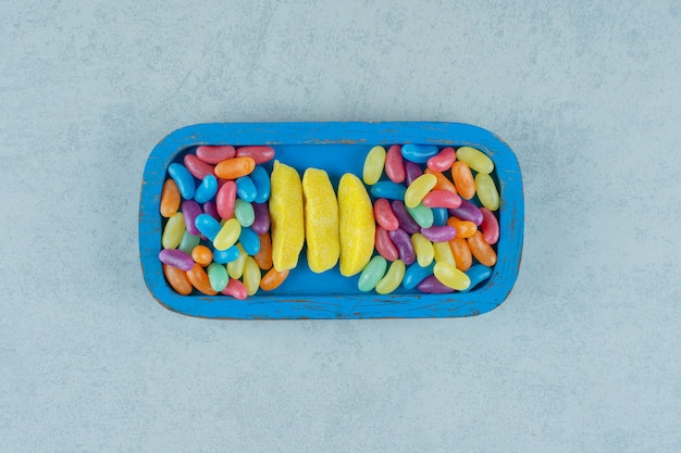 Uma placa de madeira azul com balas de mascar em forma de banana e balas de feijão coloridas