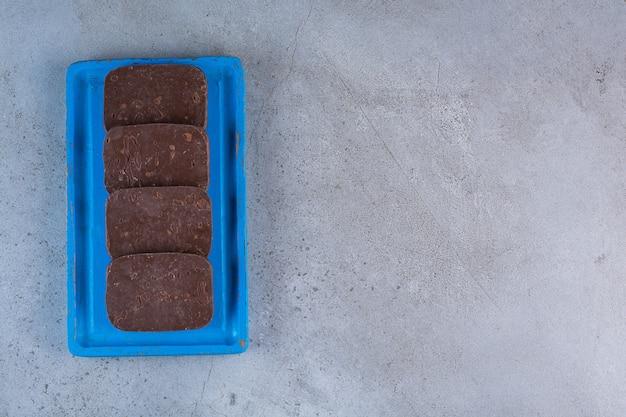 Uma placa de madeira azul com biscoitos de chocolate em um fundo cinza