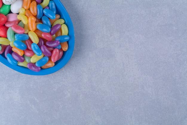 Uma placa de madeira azul com doces coloridos de geleia