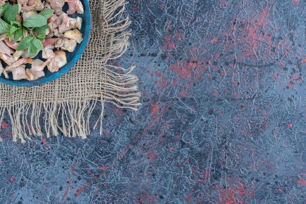 Uma placa de madeira azul com fatias de carne de frango e hortelã.