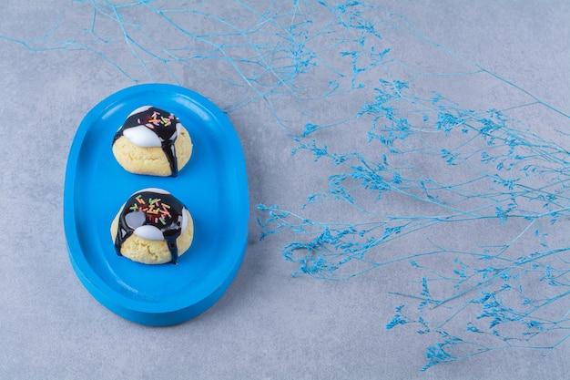 Uma placa de madeira azul de biscoitos doces com granulado colorido e calda de chocolate.
