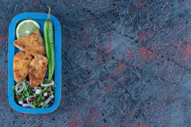 Uma placa de madeira azul de costeleta de frango assado com salada de legumes.
