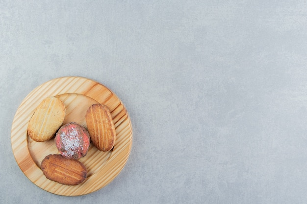 Uma placa de madeira cheia de biscoitos doces.