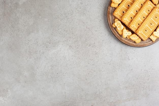 Uma placa de madeira cheia de biscoitos no fundo de mármore.