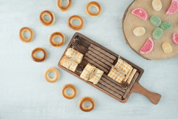 Uma placa de madeira cheia de bolos e marmelada em fundo branco. foto de alta qualidade