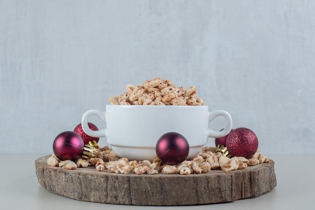 Uma placa de madeira cheia de cereais saudáveis com bolas de natal.