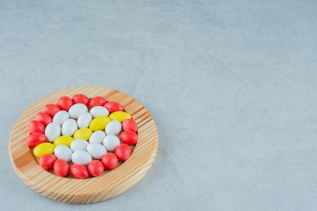 Uma placa de madeira cheia de doces coloridos doces redondos na superfície branca