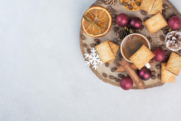 Uma placa de madeira cheia de frutas secas e uma xícara de café no fundo branco. foto de alta qualidade