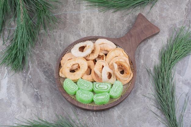 Uma placa de madeira cheia de maçãs secas e marmelada de açúcar no fundo de mármore.