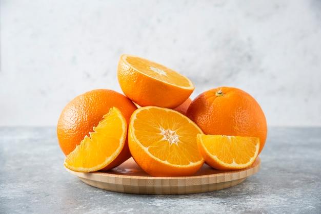Uma placa de madeira cheia de suculentas fatias de fruta laranja na mesa de pedra.
