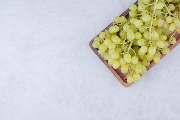 Uma placa de madeira cheia de uvas doces em fundo branco. foto de alta qualidade