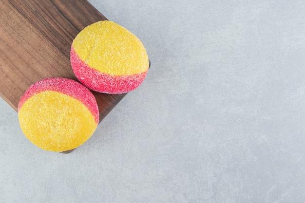 Uma placa de madeira com biscoitos doces coloridos.