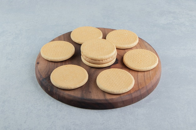 Uma placa de madeira com biscoitos doces redondos.