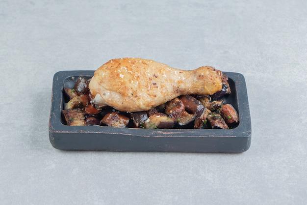 Uma placa de madeira com carne de coxa de frango frito e berinjela.