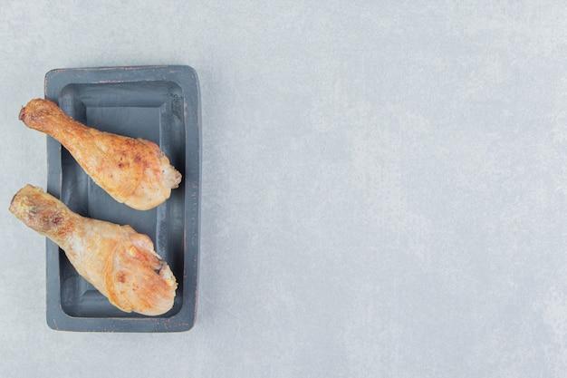 Uma placa de madeira com carne de coxas de frango frito.