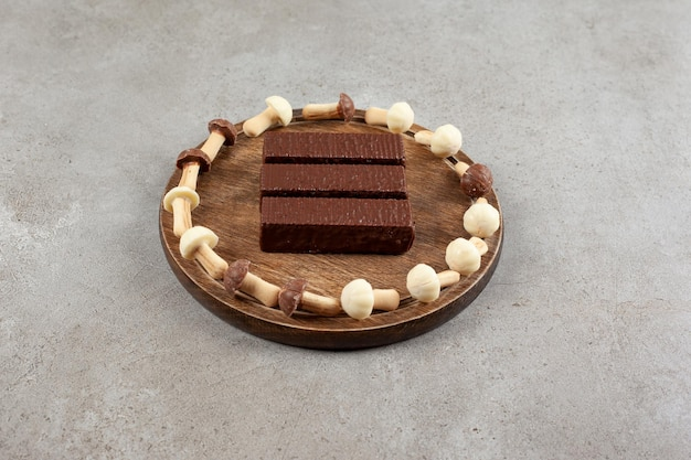Uma placa de madeira com chocolates e tigela de madeira com cogumelos doces.