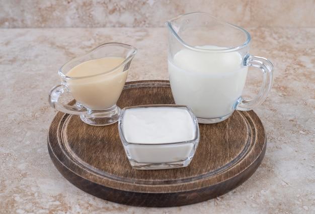 Uma placa de madeira com copos de leite de vidro