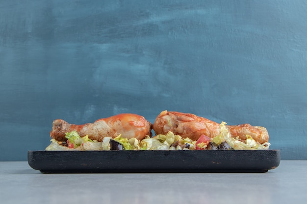 Uma placa de madeira com coxas de frango frito e salada de legumes.