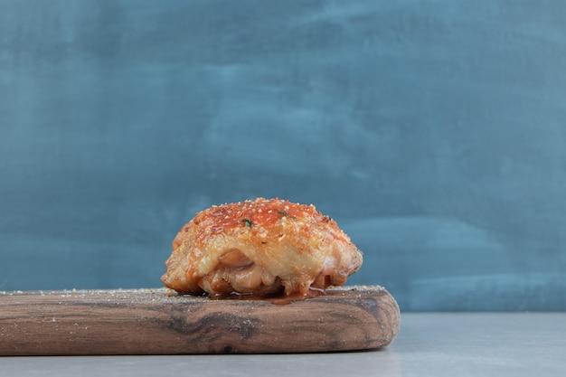 Uma placa de madeira com deliciosa carne de frango frito.
