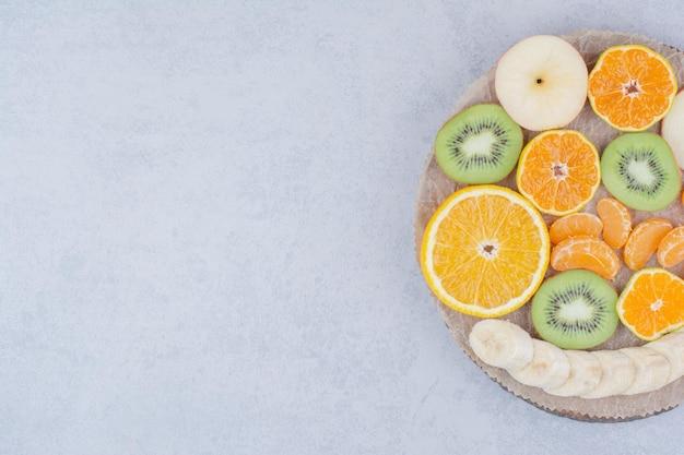 Uma placa de madeira com frutas fatiadas no fundo branco. foto de alta qualidade