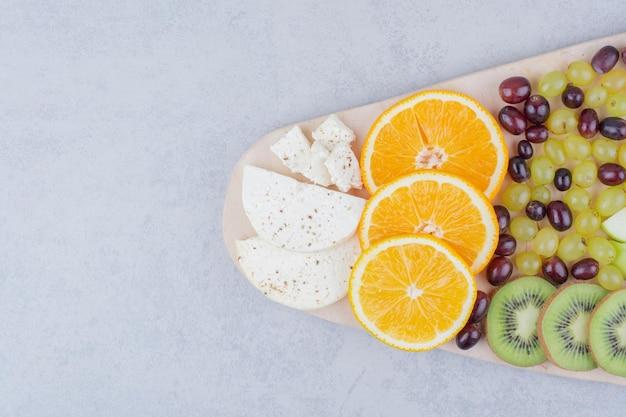 Uma placa de madeira com frutas frescas em fundo branco. foto de alta qualidade